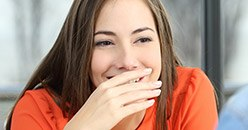 Laughing young woman covering her mouth
